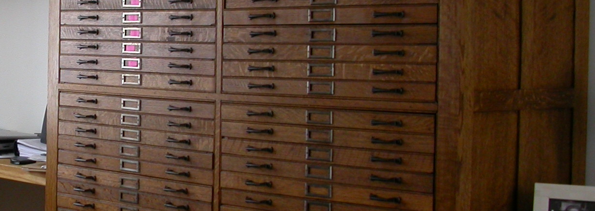 Oak printer's type-storage cabinets, used as anchors for a large White Oak desk, and to house a coin collection.